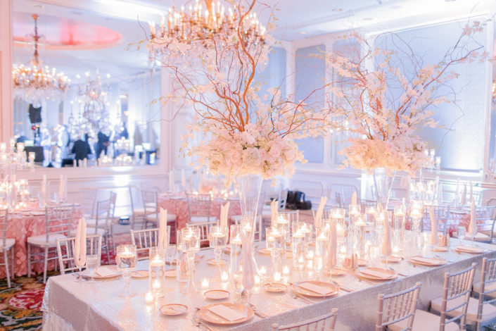 An elegantly arranged table is set with glassware, floral arrangements and candles