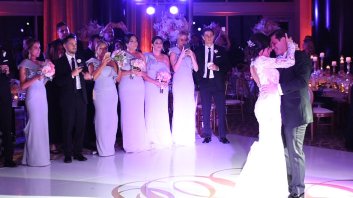 A bride and groom enjoy their first dance as guests look on
