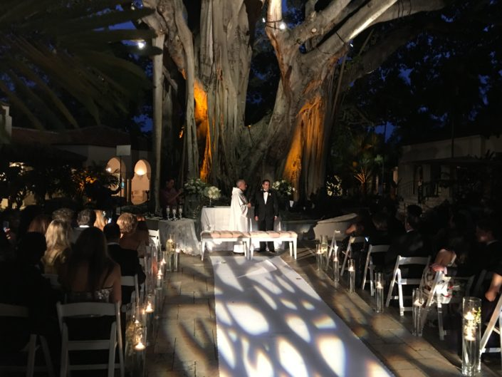 Groom stands at the end of the aisle with the officiant at an outdoor, South Florida night time wedding