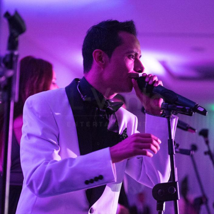 A wedding singer from Al-Vento Entertainment performs in a tuxedo during a wedding reception