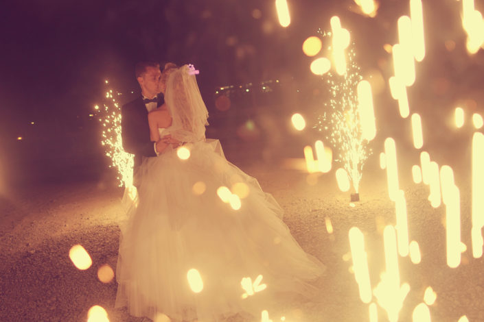 Bride and Groom kiss during fireworks show