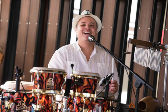 Cuban Latin Band percussionist smiling while playing
