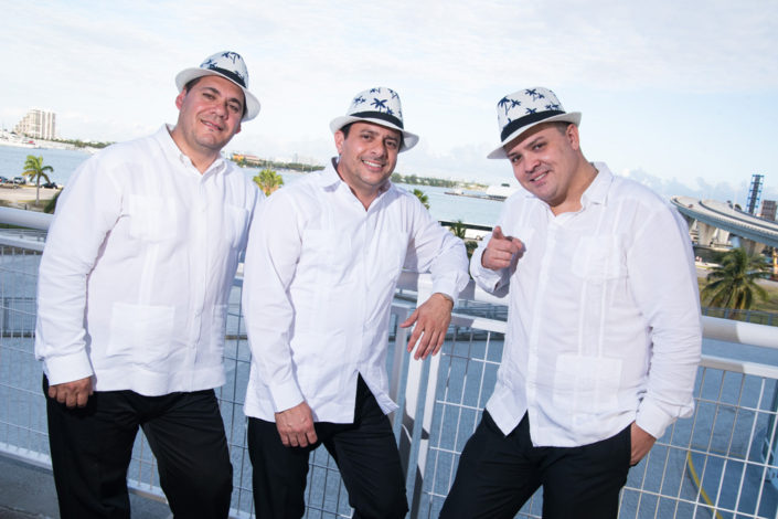 Three members of The Cuban Latin Band posing on a balcony, overlooking Biscayne Bay