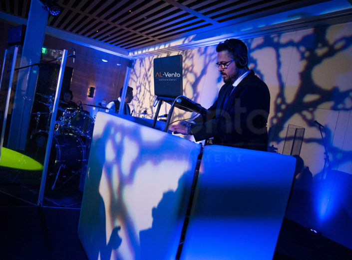 DJ Fusion plays an event with blue mood lighting.