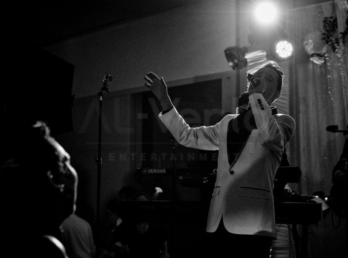Black and white image of a male singer from Social Sound performing with hands in the air at a social event